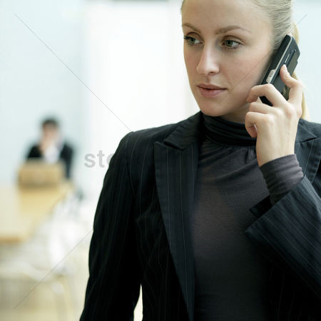 Business suit : Lady using cell phone  a guy sitting at the back