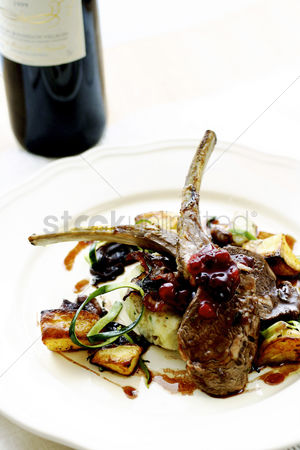 Wine bottle : Lamb chop and cranberries with wine on the background