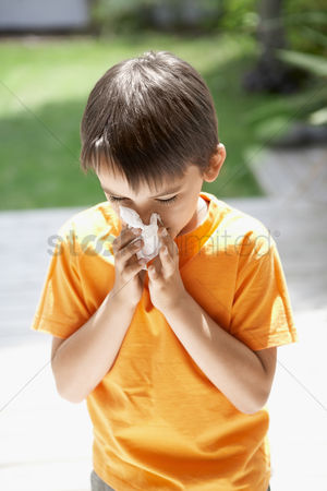 Blowing : Little boy blowing his nose in back yard