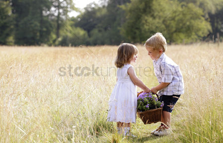 Children playing : Little boy helping little girl with the basket of flowers