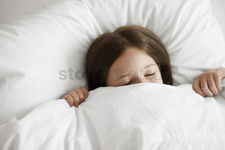 Furniture : Little girl in bed with covers pulled up over face  close up high angle view