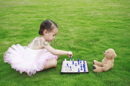 Grass : Little girl playing chess with toy bear