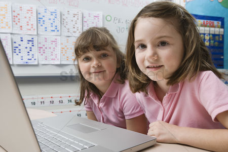 Children : Little girls using a laptop