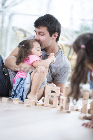 Kissing : Loving father kissing daughter building blocks on floor