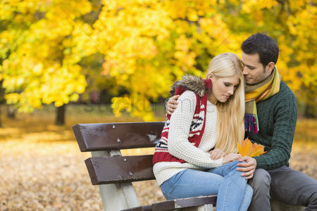 Shyness : Loving young man hugging shy woman on park bench during autumn
