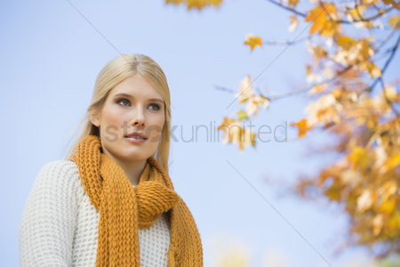 Winter : Low angle view of thoughtful young woman against sky