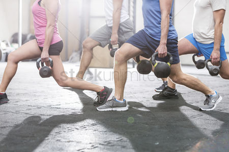 Sports : Low section of people lifting kettlebells at crossfit gym