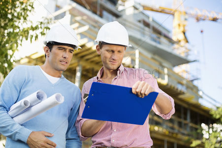Supervisor : Male architects with blueprint and clipboard working at site