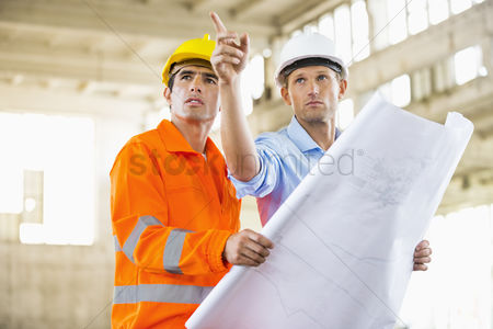 Two people : Male architects with blueprint working at construction site