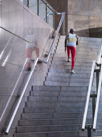 Staircase : Male athlete running up staircase outside building