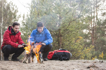 Jacket : Male backpackers warming hands at campfire in forest