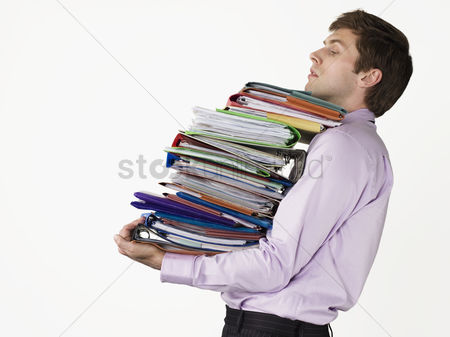Pile : Male office worker carrying heavy binders on white background