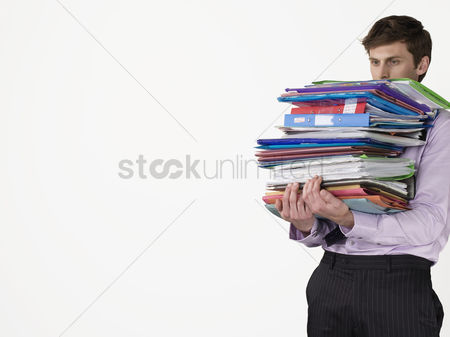 Office worker : Male office worker carrying heavy binders on white background
