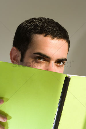Shyness : Male student hiding behind a book