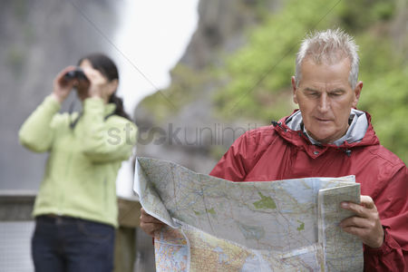 British ethnicity : Man and woman in mountains man reading map woman looking through binoculars