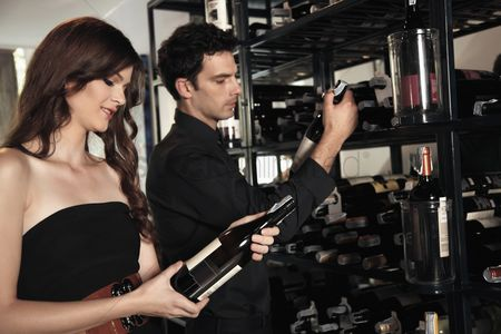 Choosing : Man and woman selecting wine bottles from rack