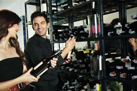 Wine bottle : Man and woman selecting wine bottles from rack