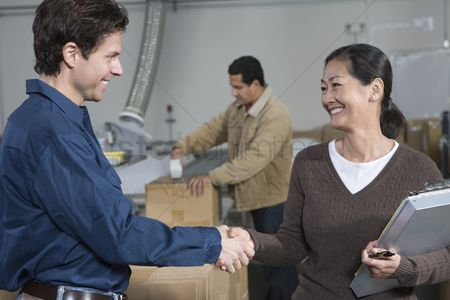 Interior background : Man and woman shaking hands in distribution warehouse