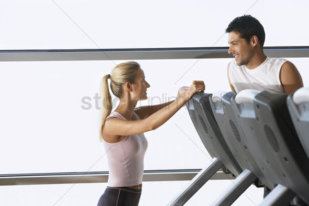 Fitness : Man and woman talking by treadmill in health club