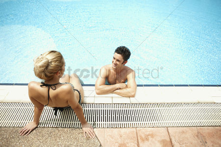 Satisfaction : Man and woman talking while relaxing by the poolside