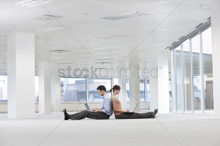 Two people : Man and woman using laptops in empty office space