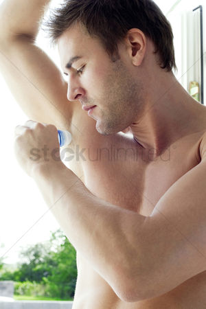 Arm raised : Man applying deodorant on his underarm