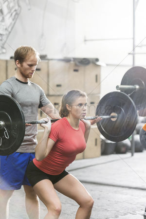 Three quarter length : Man assisting woman in lifting barbell in crossfit gym