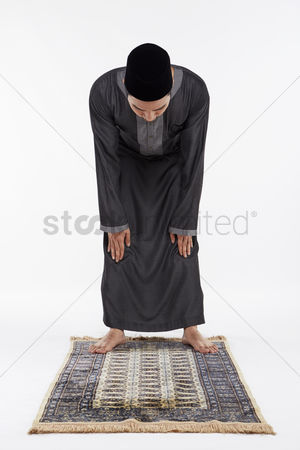 Religion : Man bending at the waist until his palms touch his knees  staying still