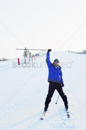 Cold temperature : Man cheering while skiing