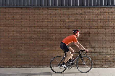 Transportation : Man cycling past brick wall