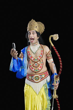 God : Man dressed-up as rama reading text message