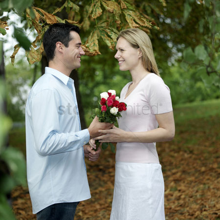 Three quarter length : Man giving his girlfriend a bouquet of flowers