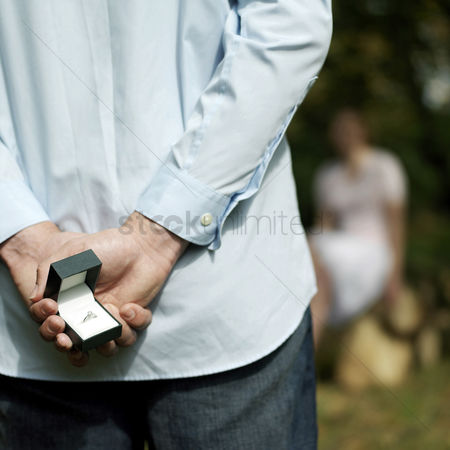 Two people : Man hiding a ring from his girlfriend
