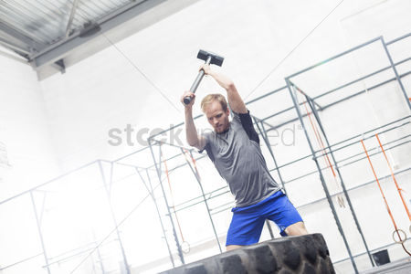 Strong : Man hitting tire with sledgehammer in crossfit gym