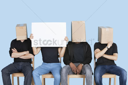 Blue background : Man holding blank cardboard with male friends faces covered with boxes over blue background
