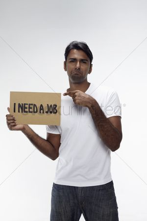 Unemployment : Man holding  i need a job  sign