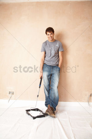 Pocket : Man holding paint roller in paint tray in unrenovated room portrait