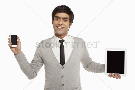 Portability : Man holding up a digital tablet and a mobile phone