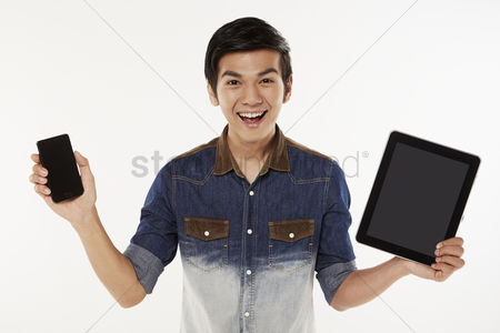 Masculinity : Man holding up a mobile phone and digital tablet