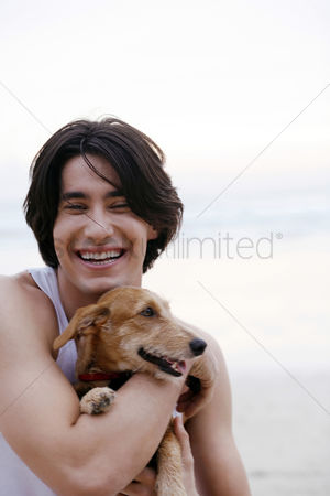 Lover : Man hugging his dog on the beach