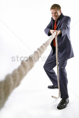 Strong : Man in business suit pulling a rope with all his might