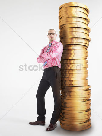 Business Finance : Man in glasses leaning against pile of coins digital composite