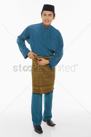 Baju melayu : Man in traditional clothing adjusting his sarong