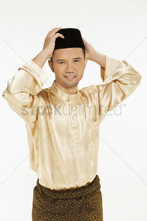 Baju melayu : Man in traditional clothing adjusting his skull cap