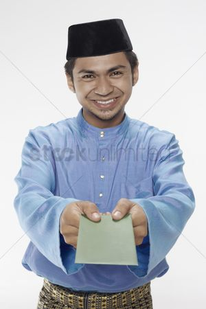 Baju melayu : Man in traditional clothing giving green packet