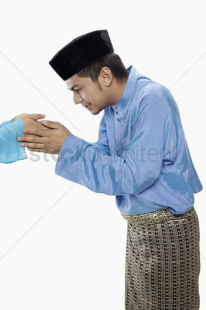 Baju melayu : Man in traditional clothing greeting another person