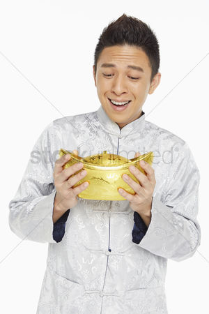 Lunar new year : Man in traditional clothing holding a gold ingot