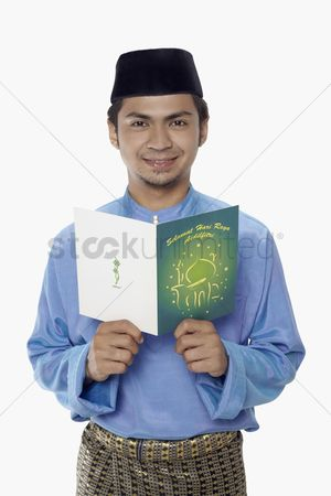 Baju melayu : Man in traditional clothing holding a greeting card