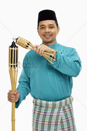 Traditional clothing : Man in traditional clothing lighting up the bamboo torches