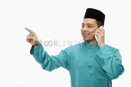 Baju melayu : Man in traditional clothing pointing while talking on mobile phone